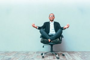 man on office chair meditating