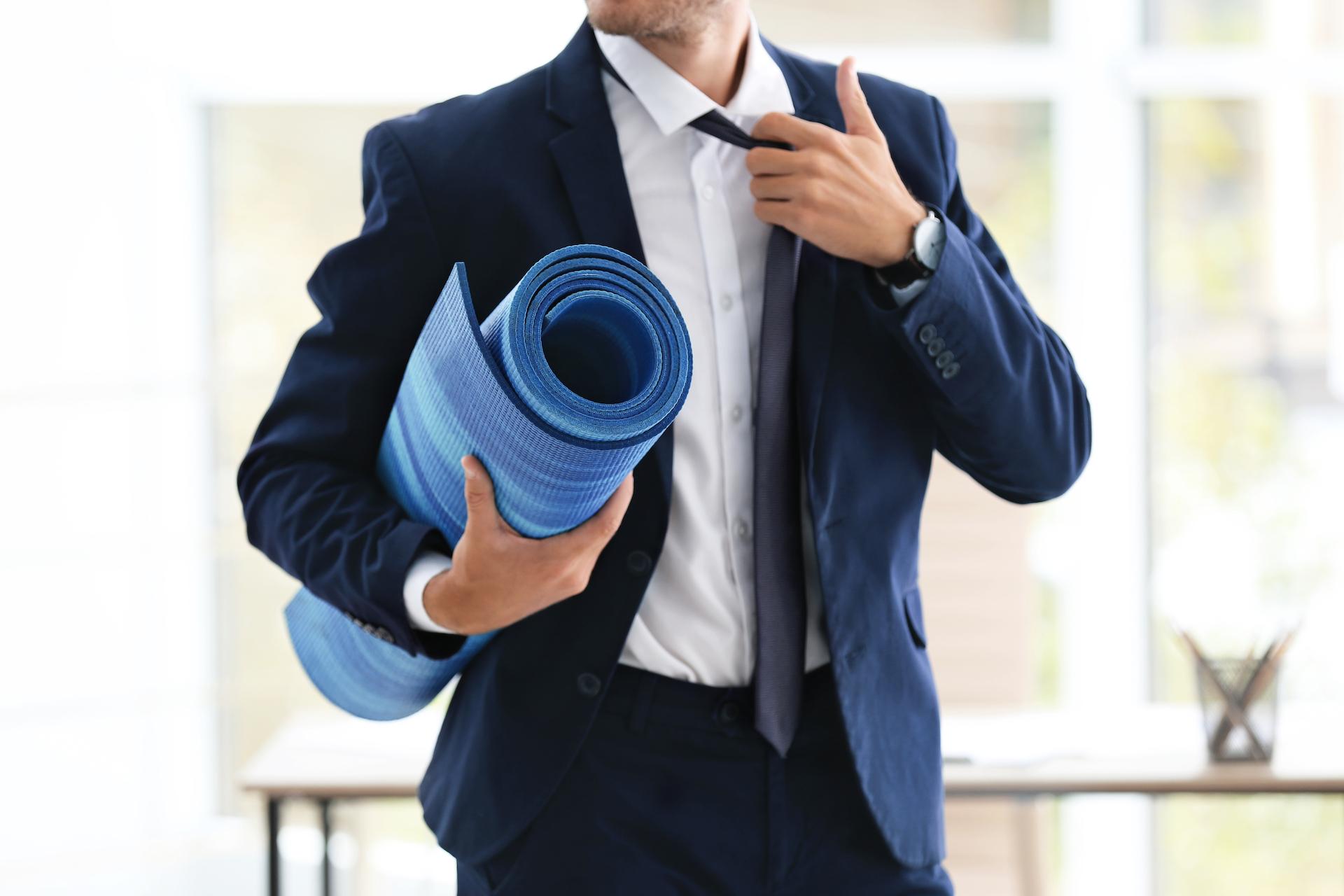 business man carrying yoga mat